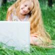allvarliga ser liten flicka med laptop — Stockfoto