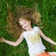 Smiling little girl in green grass — Stock Photo