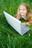 Cute little girl with laptop — Stock Photo