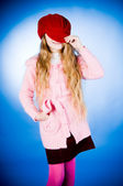 Funny little girl putting on red cap — Stock Photo