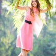 Young happy woman in pink dress — Stock fotografie