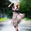 Young woman walking with umbrella — Stock Photo