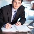 Young businessman signing a document — Stockfoto