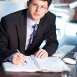 Stock Photo: Young businessman signing a document