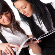 Two young women reading magazine — ストック写真