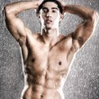 Young muscular man under the rain — Stock Photo