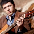 Young man playing on guitar — Stock Photo