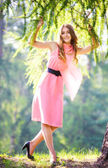 Young happy woman in pink dress — Stock Photo
