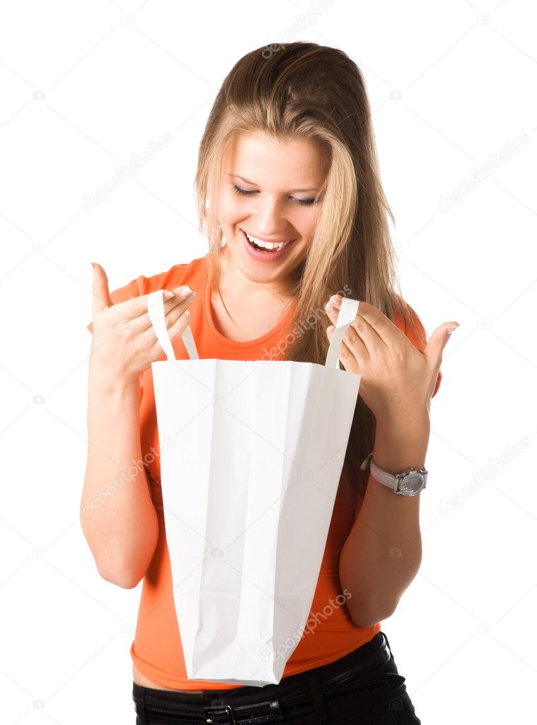 Young smiling woman looking into shopping bag. Isolated on white. — Lizenzfreies Foto #1195060