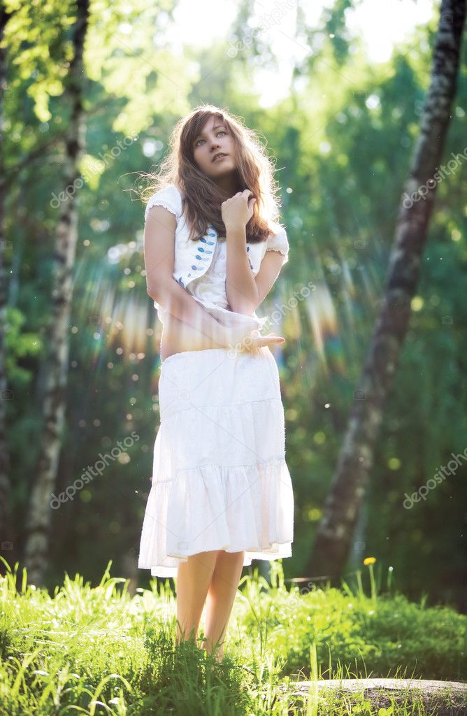 Young romantic woman standing in sun rays.  Stock Photo #1195412