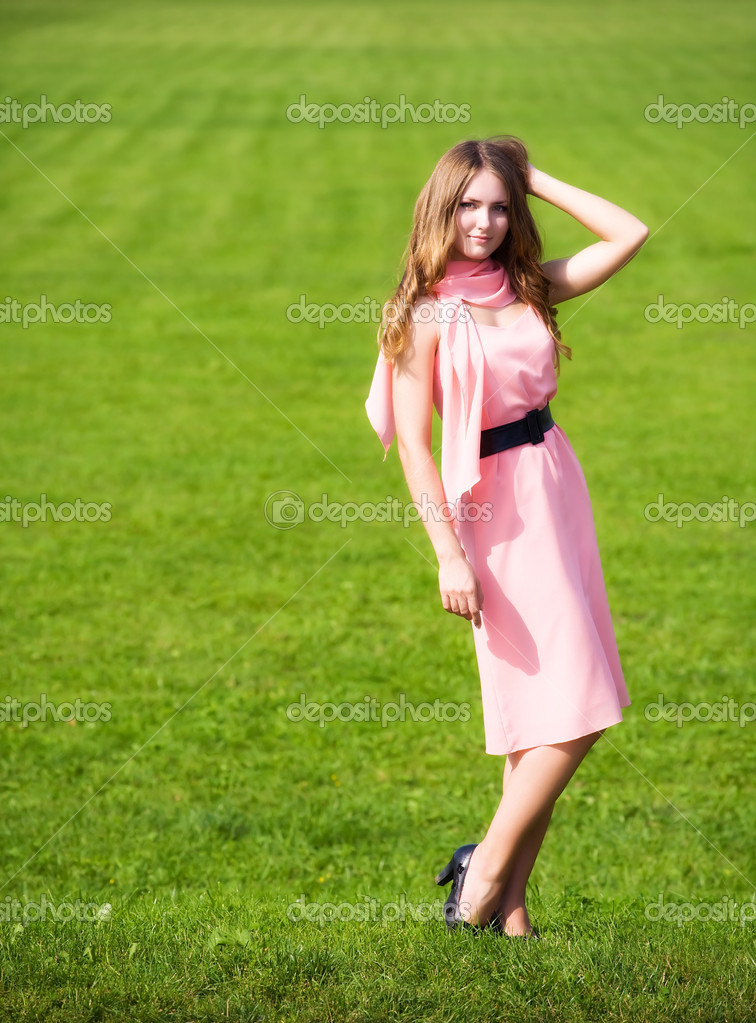 Woman in pink dress on green grass background.  Stock Photo #1328756
