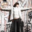 Slim woman on graffiti wall background - Stock Photo