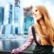 Young woman on modern city background — Foto Stock