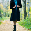 Slim brunette woman walking in a park — Stockfoto