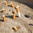 Cigarettes in sand - Stock Photo