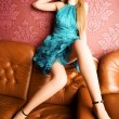 Young sexy woman on a luxury sofa — Stock Photo