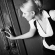 Young woman touching old door — Stock Photo