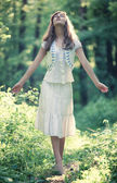 Young woman walking in a forest — Stock Photo