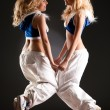 Two young women jumping - Stock Photo