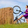 Young womwith bicycle at field — Stock Photo #1362406