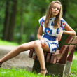 Young woman sitting on a bench — Stock Photo #1369011