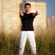 Young man showing success handsign - Stok fotoğraf