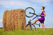 Young woman with bicycle at the field — Stock Photo