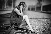 Young woman sitting on a rails — Stock Photo