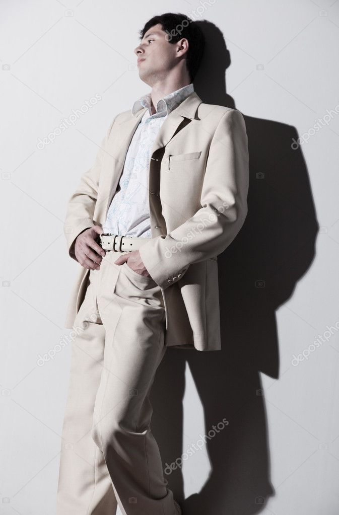 Young handsome man in white suit. On white wall background. — Stock Photo #1362290