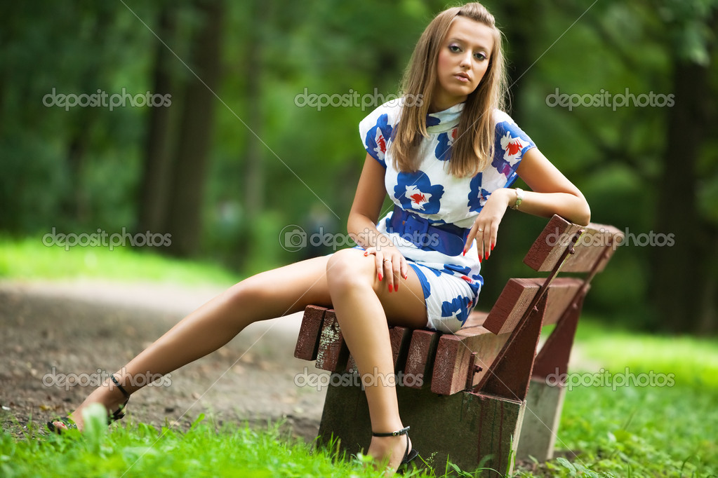 Young woman sitting on a bench in a park. — Stock Photo #1369011