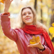 Young woman throwing leaves — Stock Photo