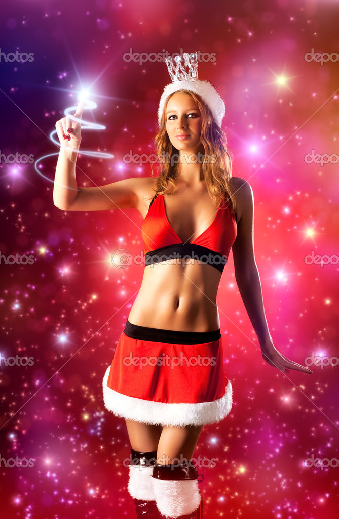 Young sexy woman in santa clothing seting the star. — Stock Photo #1372862