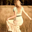 Joyful girl walking on a field — Stockfoto