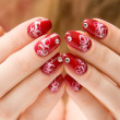 Red woman nails with decorations — Stock Photo #1676285