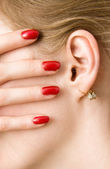Red woman fingers and ear — Stock Photo