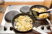 Frying potatoes on two pans — Stock Photo