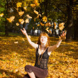 Woman throwing autumn maple leaves — Stock Photo
