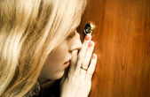 Woman looking into spy hole — Stock Photo