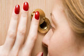 Woman looking into spy hole closeup — Stock Photo