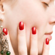 Young woman face and hand with red nails — Stock Photo
