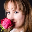 Young woman smelling red rose — Stock Photo