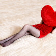 Young woman holding red heart pillow — Stock Photo
