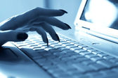 Woman hand on laptop keyboard — Stock Photo