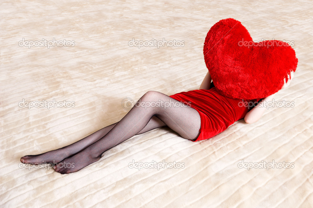 Young sexy woman on big counterpane holding red heart pillow. — Stock Photo #1715117