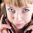 Woman speaking on two mobile phones — Stockfoto