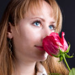 Young woman smelling red rose. — Stock Photo