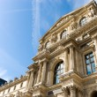 Louvre building on blue sky background - Stock Photo