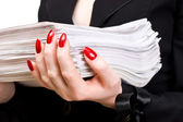 Businesswoman holding heap of papers — Stock Photo