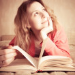 Stock Photo: Girl dreams reading the book