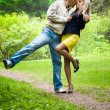 Foto Stock: Young happy couple kissing in a park